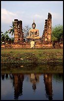 Buddha image reflected in moat, morning, Wat Mahathat. Sukothai, Thailand (color)