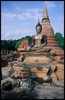 Classic sitting Buddha image and tiered, bell-shaped chedi. Sukothai, Thailand