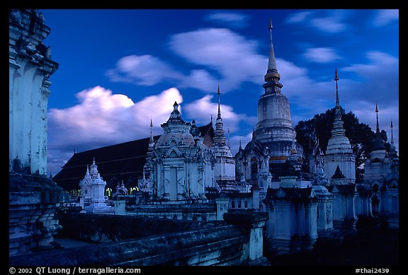Chedis in blue light with bright clouds, Wat Suan Dok, dusk. Chiang Mai, Thailand (color)