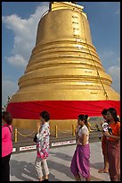 Worshippers circle around chedi. Bangkok, Thailand