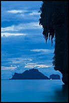 Limestone crag with stalactite, distant islet, boat light, Railay. Krabi Province, Thailand ( color)