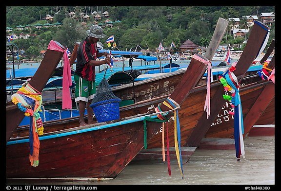 Row of boats, fisherman standing, Ko Phi Phi. Krabi Province, Thailand (color)