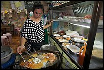 Woman adding spices to Pad Thai, Ko Phi-Phi island. Krabi Province, Thailand (color)