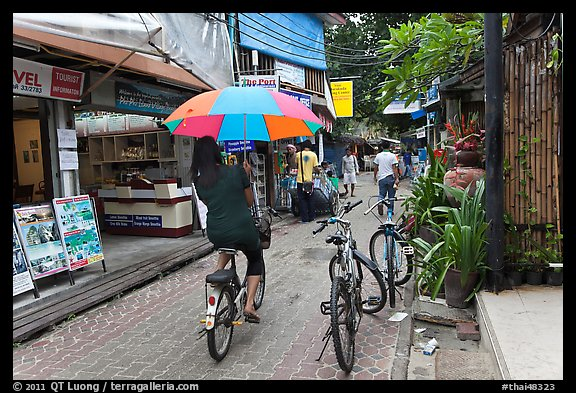 Woman riding bicycle with unbrella, Tonsai village, Ko Phi-Phi Don. Krabi Province, Thailand (color)