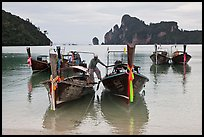 Man stepping on boats, Ao Lo Dalam, Ko Phi-Phi Don. Krabi Province, Thailand (color)