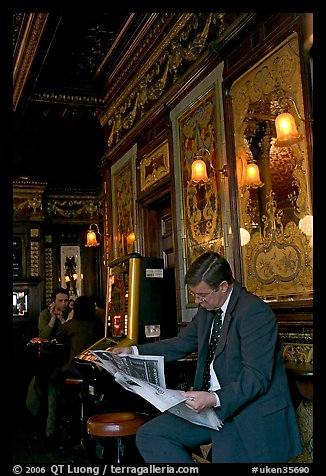 Man reading newspaper in front of etched mirrors, pub Princess Louise. London, England, United Kingdom (color)