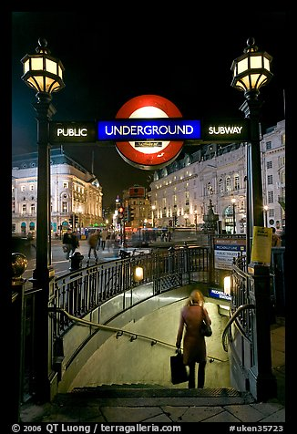 Woman with shopping bag entering subway at night, Piccadilly Circus. London, England, United Kingdom
