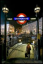Woman with shopping bag entering subway at night, Piccadilly Circus. London, England, United Kingdom (color)