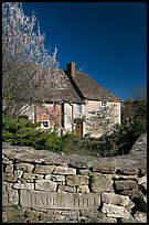 Stone wall with engraved street name, yard and house, Lacock. Wiltshire, England, United Kingdom