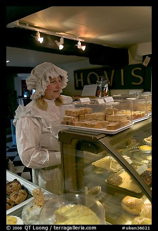 Woman wearing old-fashioned attire in a bakery, Lacock. Wiltshire, England, United Kingdom (color)