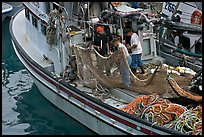 Fishermen repairing nets on fishing boat. Whittier, Alaska, USA ( color)