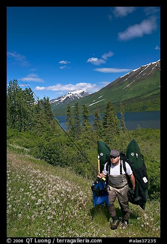 Fisherman hiking out from lake with full gear. Alaska, USA (color)