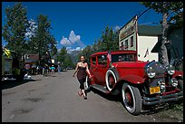 Woman walking next to red classic car. McCarthy, Alaska, USA ( color)