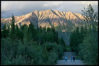 People walking on unpaved road, with last light on mountains. McCarthy, Alaska, USA (color)