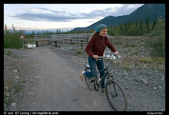 Woman on mountain bike with bridge behind. McCarthy, Alaska, USA (color)