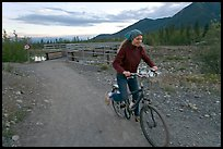 Woman on mountain bike with bridge behind. McCarthy, Alaska, USA ( color)