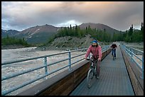 Mountain bikers crossing Kennicott River Footbridge at sunset. McCarthy, Alaska, USA ( color)