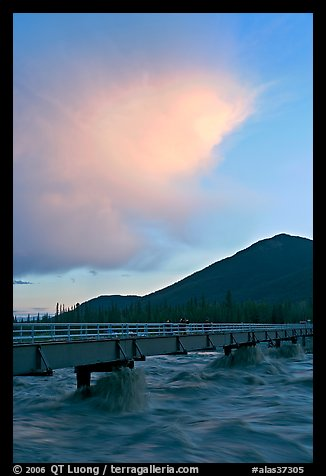 Footbridge with the Kennicott River swelled from the annual Hidden Lake flood. McCarthy, Alaska, USA (color)