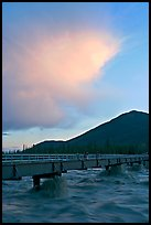 Footbridge with the Kennicott River swelled from the annual Hidden Lake flood. McCarthy, Alaska, USA