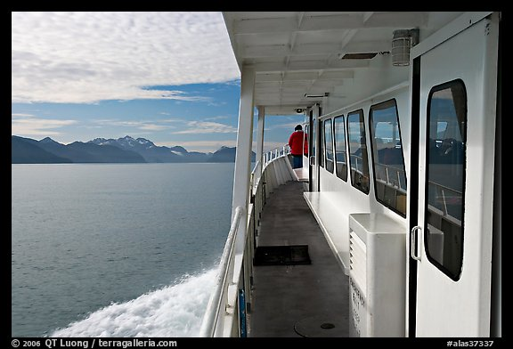 Passenger standing outside tour boat. Seward, Alaska, USA (color)