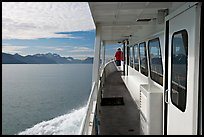 Passenger standing outside tour boat. Seward, Alaska, USA