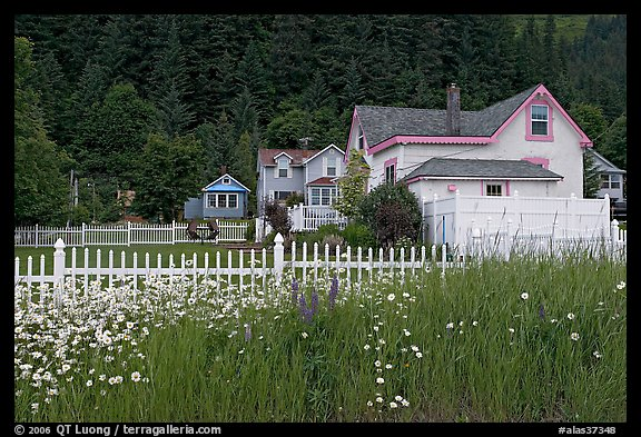 White picket fence and houses with pastel trims. Seward, Alaska, USA (color)