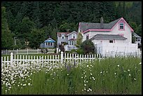 White picket fence and houses with pastel trims. Seward, Alaska, USA