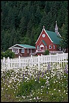 White flowers,  picket fence, red church, and forest. Seward, Alaska, USA
