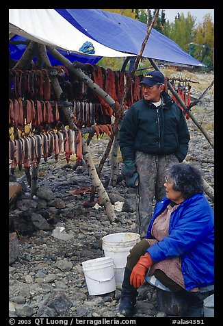 Inupiaq Eskimo man and woman next to fish hung for drying, Ambler. North Western Alaska, USA (color)