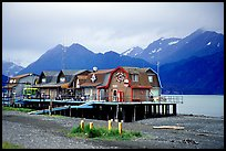 Stilt houses on the Spit, Kenai Mountains in the backgound. Homer, Alaska, USA (color)