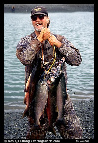 Man carrying salmon freshly caught in the Fishing Hole. Homer, Alaska, USA (color)