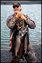 Man carrying salmon freshly caught in the Fishing Hole. Homer, Alaska, USA