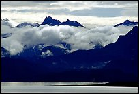 Mountains rising above bay with low clouds. Homer, Alaska, USA