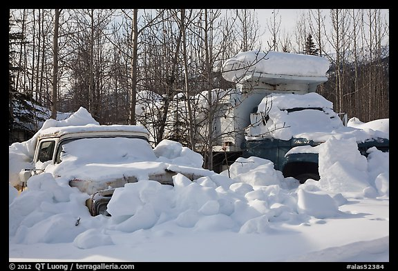 Trucks covered with piles of snow. Wiseman, Alaska, USA (color)