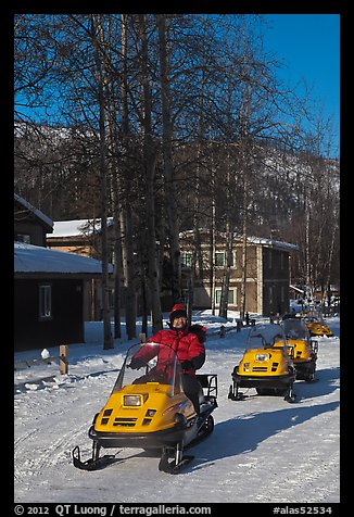 Snomobiler next to resort buildings. Chena Hot Springs, Alaska, USA (color)