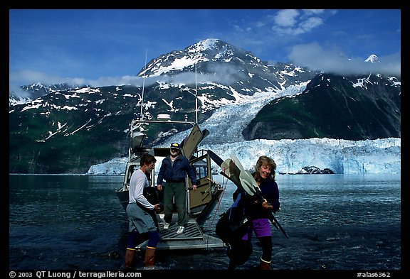 Kayakers unloading kayak from water taxi boat at Black Sand Beach. Prince William Sound, Alaska, USA (color)