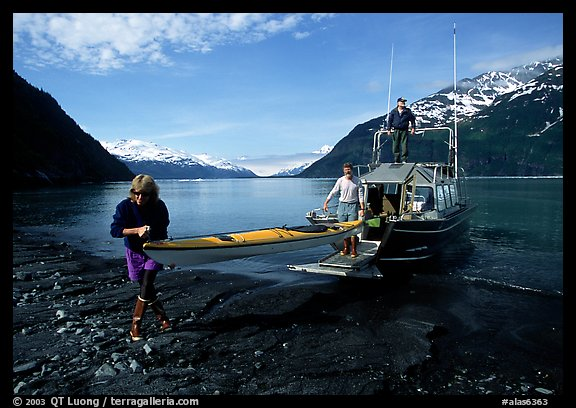 Man and woman carry kayak out of small boat at Black Sand Beach. Prince William Sound, Alaska, USA (color)