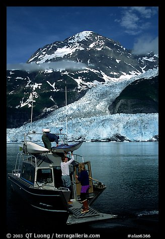 Kayakers unloading from the water taxi at Black Sand Beach. Prince William Sound, Alaska, USA (color)