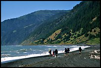 Backpackers on black sand beach and King Range, Lost Coast. California, USA (color)