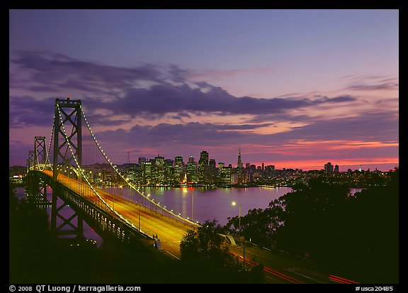 Bay Bridge and city skyline with lights at sunset. San Francisco, California, USA (color)