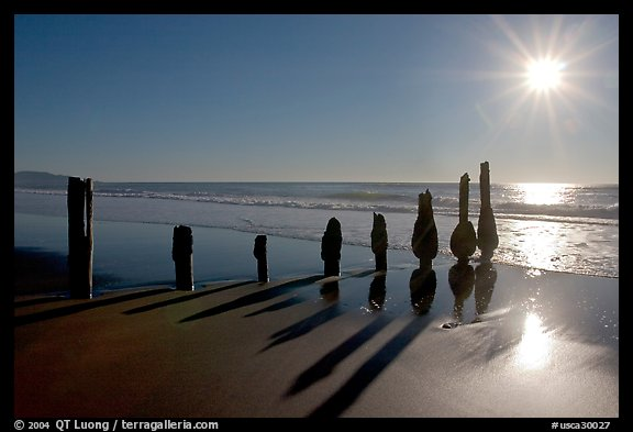 Row of wood pilars and sun near Fort Funston,  late afternoon, San Francisco. San Francisco, California, USA (color)
