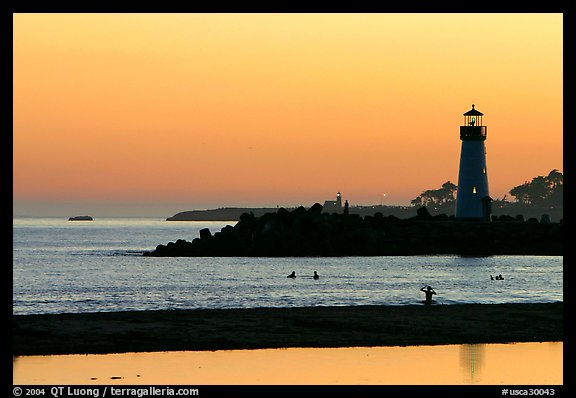 Lighthouse and Surfers in the water at sunset. Santa Cruz, California, USA (color)