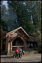 Couple sitting in front of park headquarters, afternoon. Big Basin Redwoods State Park,  California, USA (color)