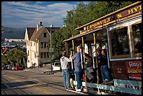 Cable car plunging with people clinging on Hyde Street, late afternoon. San Francisco, California, USA (color)