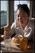 Woman eating a bown of clam chowder on the pier. Santa Cruz, California, USA