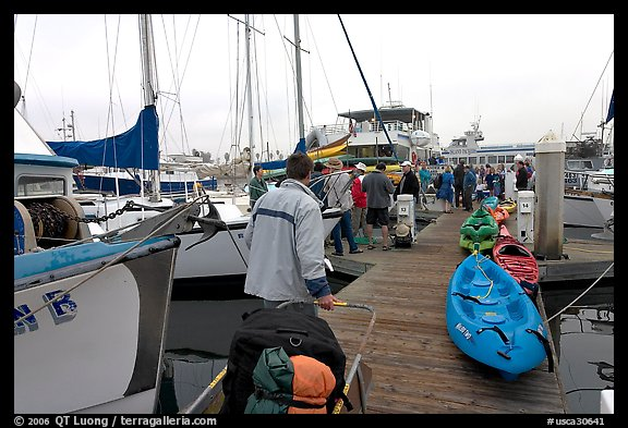 Pier with passengers preparing to board a tour boat with outdoor gear, Ventura. California, USA (color)