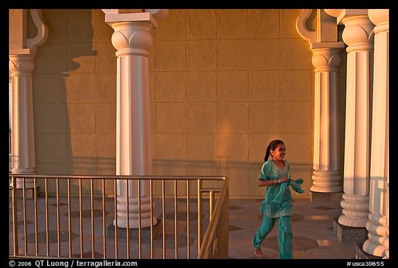 Indian girl running in the Sikh Gurdwara Temple, late afternoon. San Jose, California, USA (color)