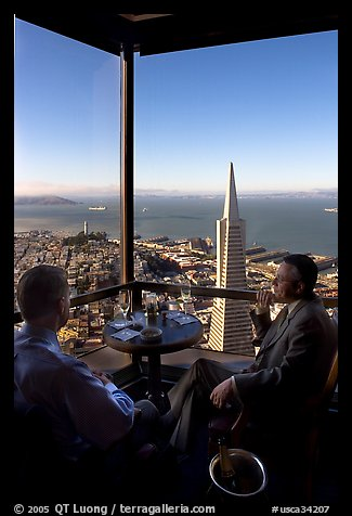Businessmen with a bottle of Champagne in the Carnelian Room with panoramic view of the City. San Francisco, California, USA