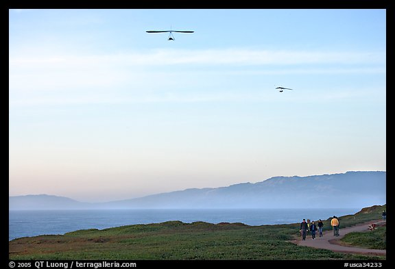 Hang gliders soaring above hikers, Fort Funston, late afternoon. San Francisco, California, USA (color)