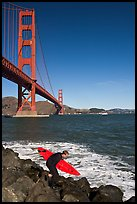 Surfer scrambling on rocks below the Golden Gate Bridge. San Francisco, California, USA